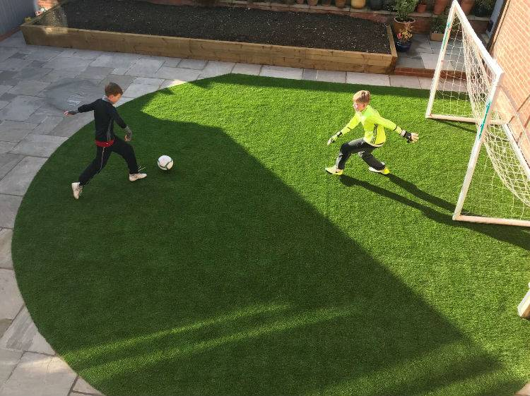Boys playing football on artificial grass